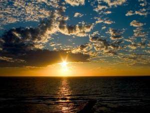 Postal: Cielo con sol y nubes sobre el mar al atardecer