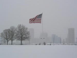 Postal: Nieve en un parque con la bandera americana