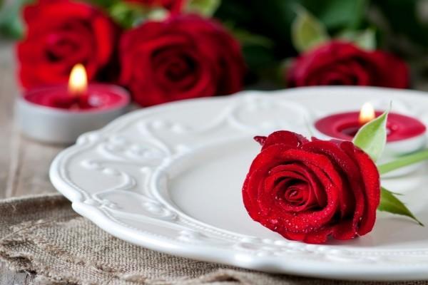 Rosa roja sobre un plato y velas