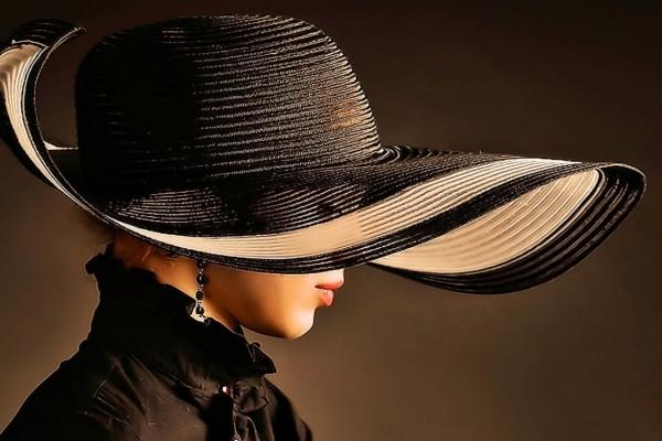 Distinguida mujer con sombrero y pendientes