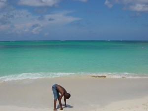 Postal: Niño jugando en la arena de la playa