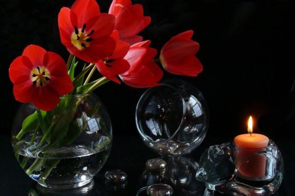 Florero de vidrio con tulipanes y una vela