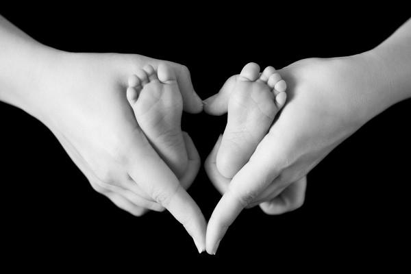 Piecitos de bebé tomados por las manos de mamá