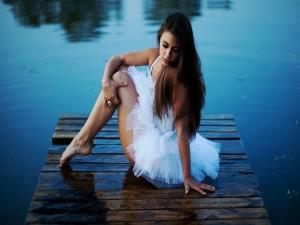 Mujer sentada junto al lago