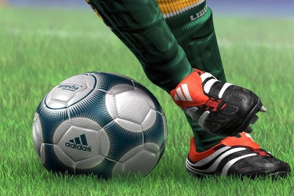 Balón y botas sobre el cesped