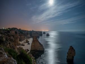 La luna iluminando las rocas y el mar