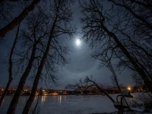 Noche de luna llena sobre el lago y la ciudad