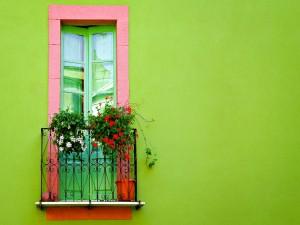 Postal: Flores en un colorido balcón