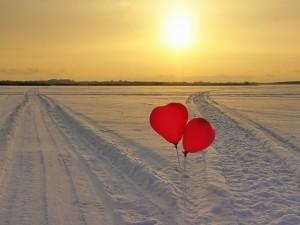 Dos globos rojos en una carretera cubierta de nieve