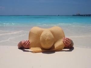 Postal: Tomando sol en la playa con un gran sombrero
