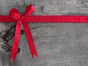 Postal: Lazo rojo sobre la madera