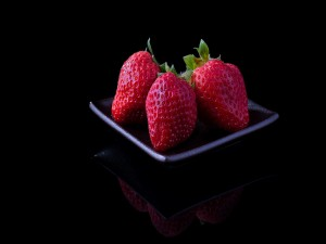 Postal: Fresas en un plato negro