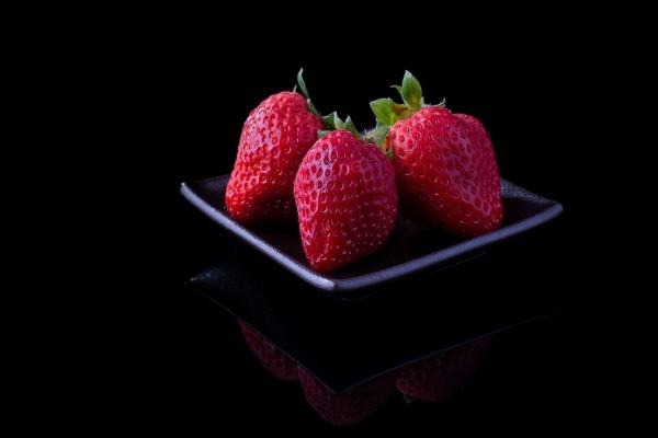 Fresas en un plato negro