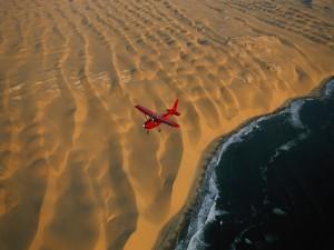 Postal: Avión sobrevolando el mar y la playa