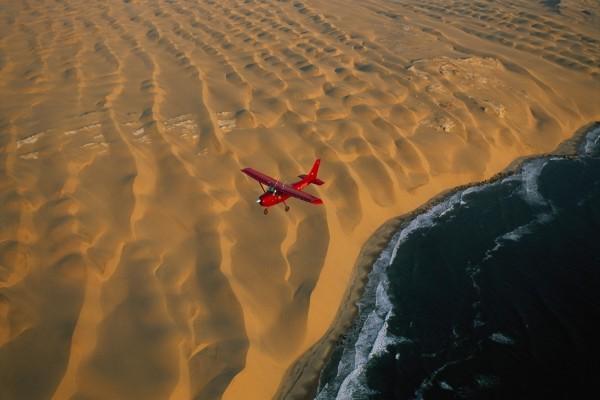 Avión sobrevolando el mar y la playa