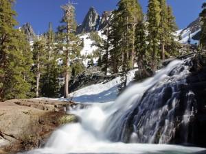Cascada entre montañas y pinos