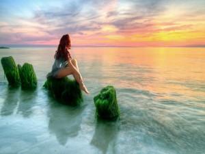 Sentada frente al mar observando la puesta del sol