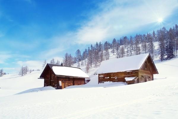 Dos cabañas de madera en la nieve