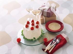 Pastel con fresas, copas y regalos para un celebración