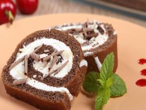 Rollo de torta con chocolate, nata, bayas y menta