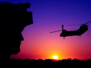 Helicóptero volando sobre la ciudad al atardecer