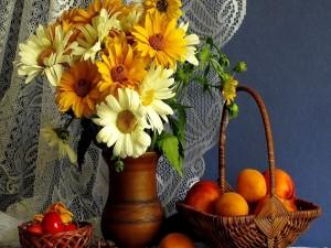 Gerberas en un florero y albaricoques en una cesta
