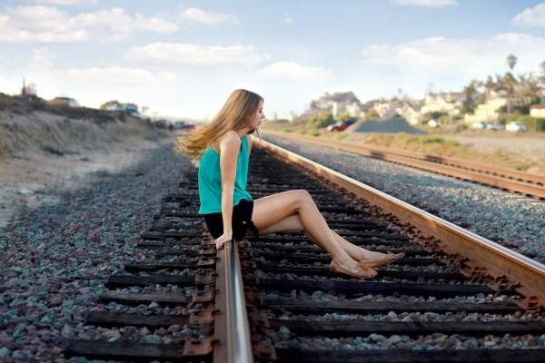 Chica sentada en la vía del tren