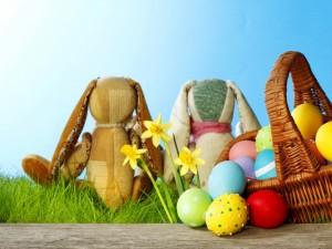 Conejitos en el prado, al lado de una cesta con huevitos de Pascua