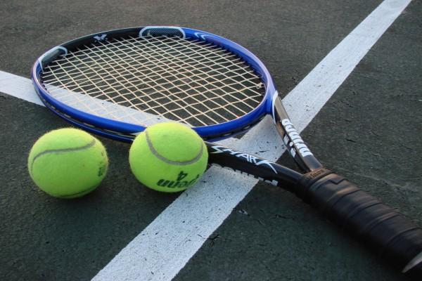 Raqueta y pelotas sobre la pista