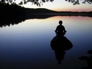 Meditando sobre una roca en el lago