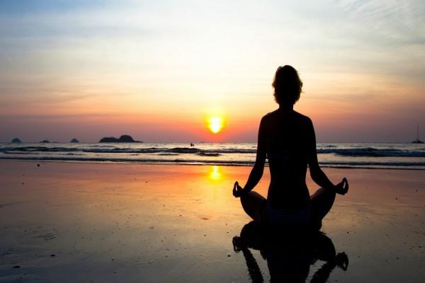 Meditando en la playa al atardecer