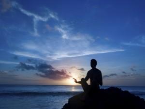 Meditando en una roca junto al mar