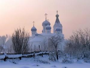 Iglesia, camino y árboles cubiertos con nieve