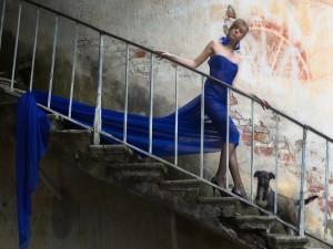 Bella mujer bajando las escaleras, con un vestido azul