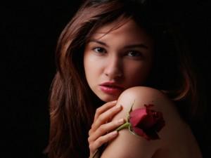 Hermosa mujer con un pimpollo de rosa