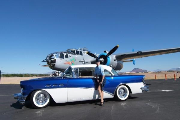 Mujer soldado junto a un bonito coche y un avión
