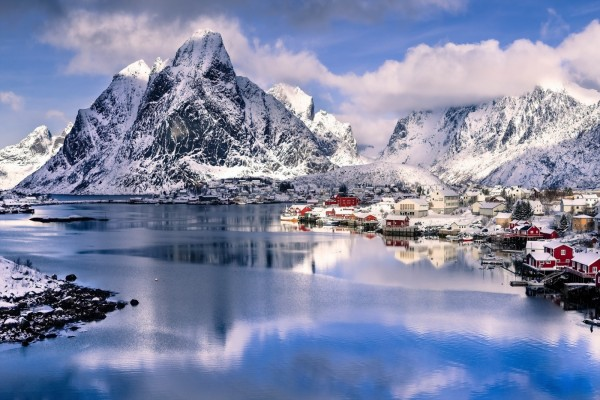 Aldea a orillas del lago y montañas cubiertas de nieve