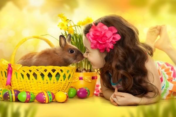 Nena con un conejito, junto a huevos de Pascua