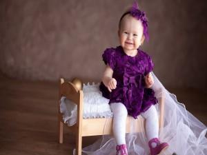 Una niña sonriente en una cunita