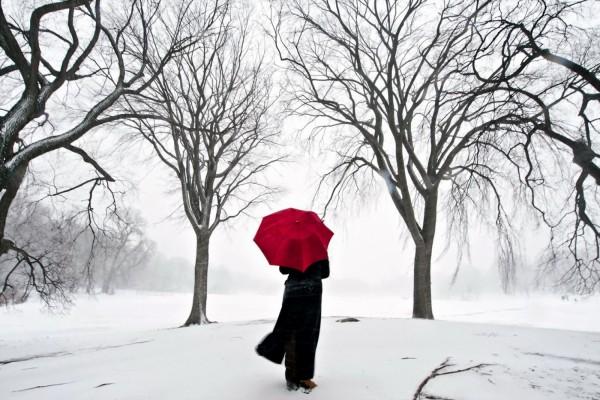 Con un paraguas rojo en la nieve