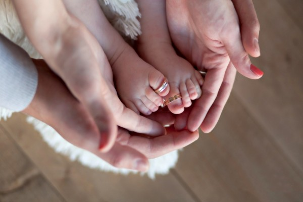 Piecitos de bebé en las manos de papá y mamá