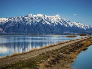 Carretera, lago y montañas nevadas