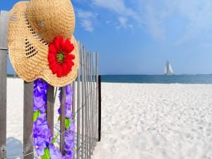 Postal: Sombrero y collar de flores en la playa
