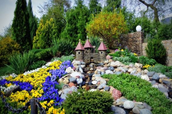 Castillo rodeado de árboles, piedras y flores