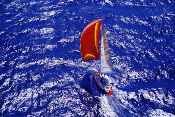 Barco con una vela roja en el mar