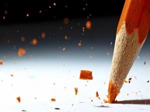 Rompiendo la punta de un lápiz naranja