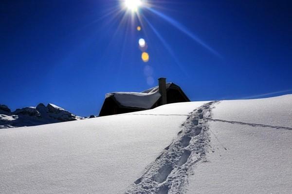Pisadas en la nieve frente a una casa