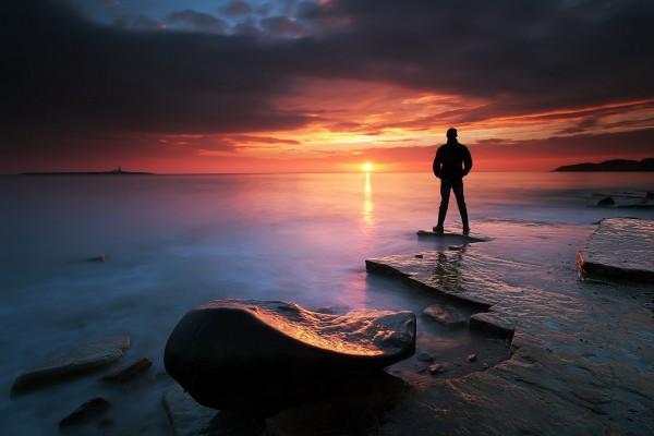 Silueta en el mar observando la salida del sol