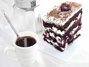 Un trozo de pastel de chocolate, nata y café