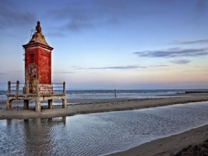 Postal: Un faro viejo a orillas del mar